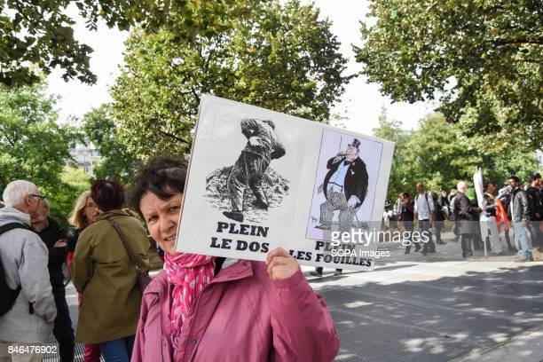 An activist holds a placard writing on it I have back pain and they are making money' take part in a protest during the nationwide strike called by...