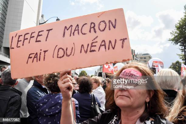 An activist holds a placard writing on it Macron effect is nothingness' take part in a protest during the nationwide strike called by various French...