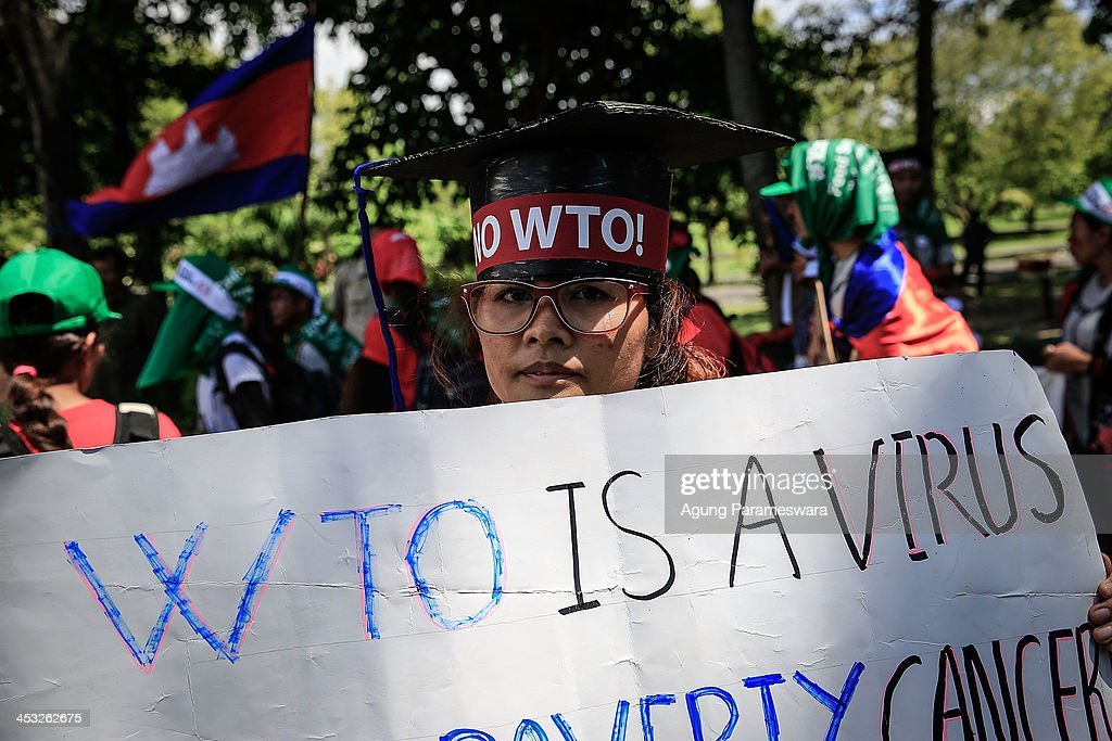 An activist holds a poster during a protest against the World Trade Organization meeting on December 3 2013 in Denpasar Indonesia Thousands of...