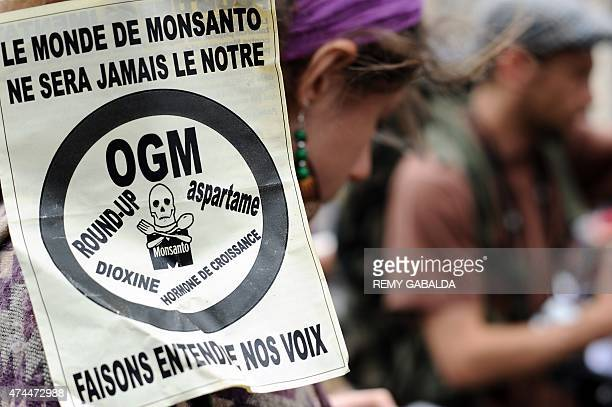 An activist holds a poster that reads 'Le monde de Monsanto ne sera jamais le notre Faisons entendre nos voix' at a march against Monsanto where...