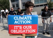An activist holds a sign as he participates in a sitin and protest against the Keystone XL pipeline outside the US State Department August 12 2013 in...