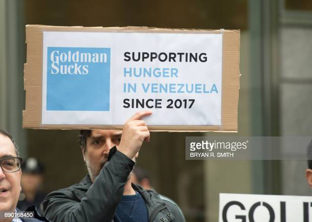 An activist holds a sign during a protest against Goldman Sach's bond purchase transaction of $28 billion with Venezuela's Nicolas Maduro outside...