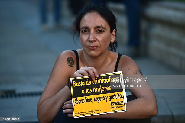 An activist holds a sign reading 'Stop criminalizing women Free and safe abortion' during a proabortion demo in front of La Moneda presidential...