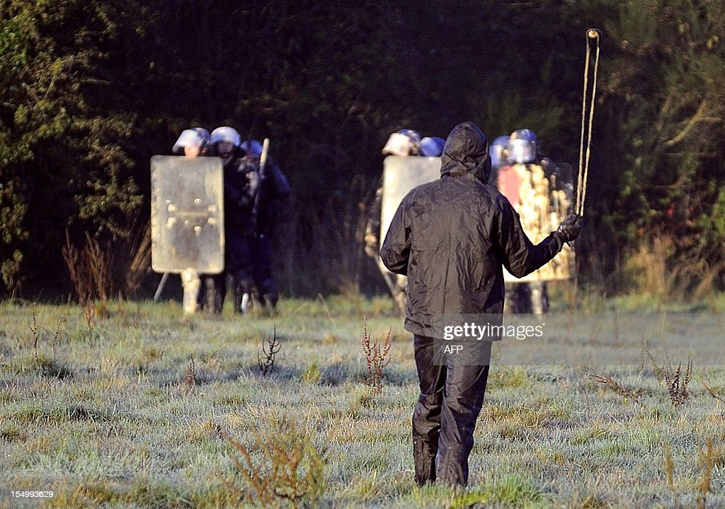 An activist holds a slingshot as he faces French Gendarmes, on October 30, 2012, during an important evacuation operation, started on October 16, of houses squatted by opponents against the project to build an international airport, in Notre-Dame-des-Landes, western France. The project was signed in 2010 and the international airport is supposed to open in 2017 near the city of Nantes.