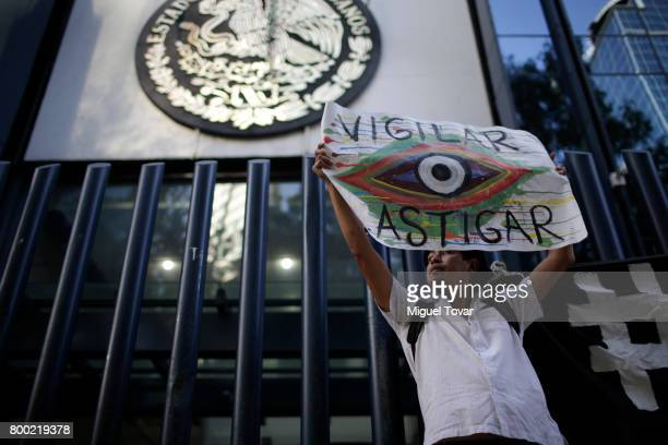 An activist holds up a banner during a demonstration against alleged government spying on journalists and human rights defenders outside the attorney...