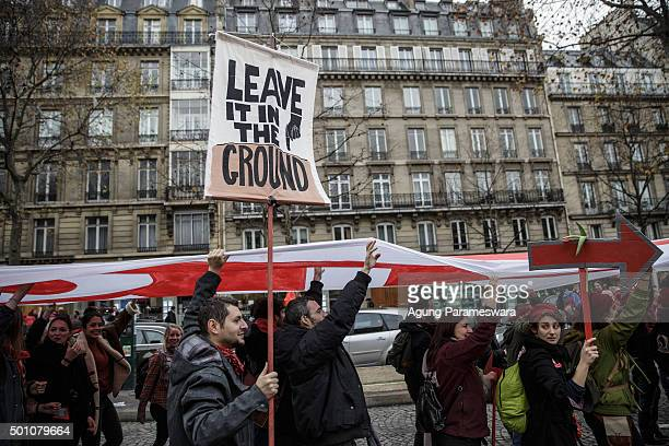An activist holds up a poster during a demonstration near the Arc de Triomphe at the Avenue de la Grande Armee boulevard on December 12 2015 in Paris...