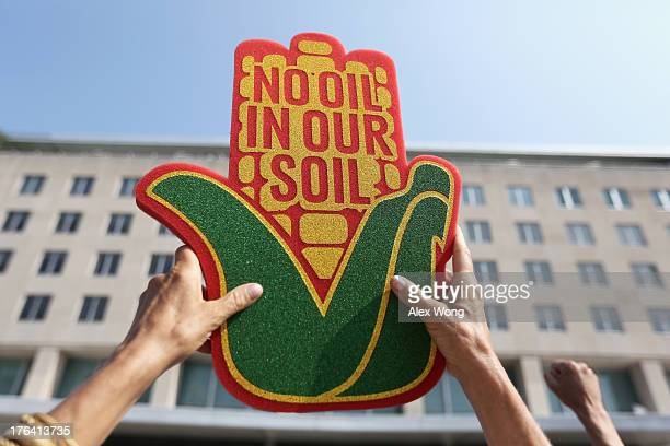 An activist holds up a sign during a sitin and protest against the Keystone XL pipeline outside the US State Department August 12 2013 in Washington...