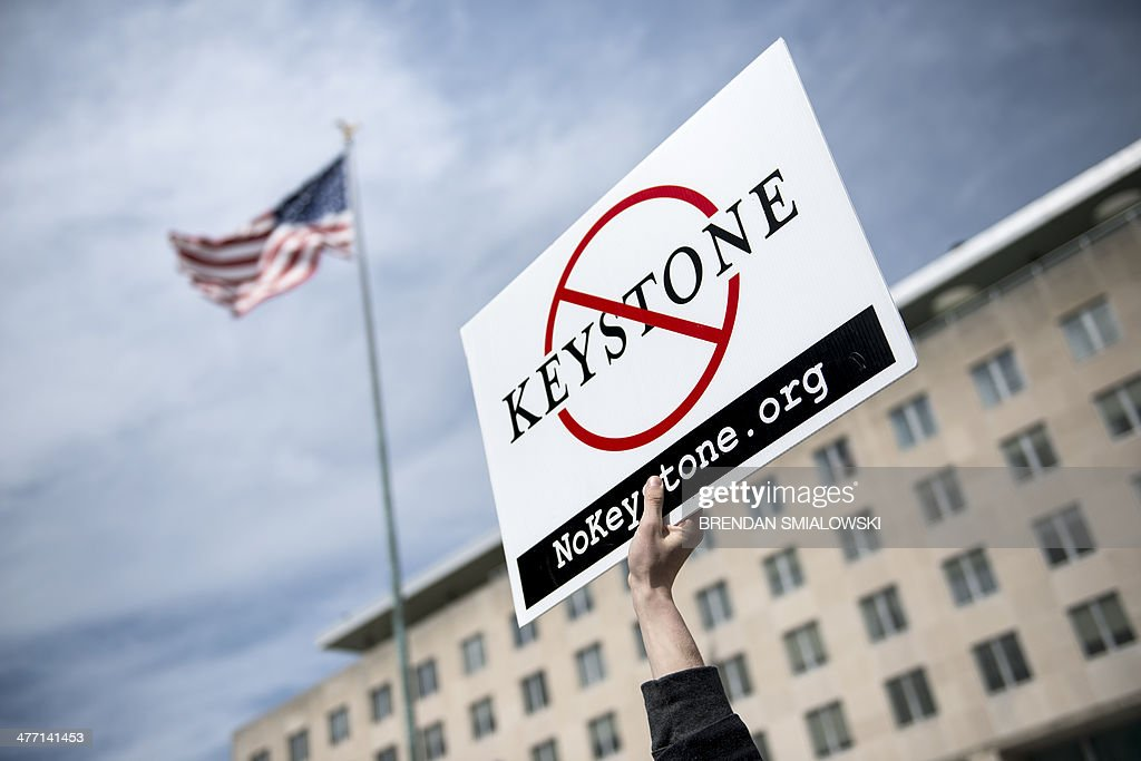An activist holds up a sign outside the State Department during a protest of the Keystone XL pipeline on March 7, 2014 in Washington. Activists organized by the Energy Action Coalition marched to the State Department to protest the construction of the pipeline which would carry tar sands oil from Canada. AFP PHOTO/Brendan SMIALOWSKI