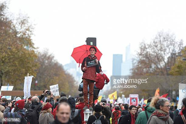 An activist holds up a sign reading in French 'I am climate' as other activists form a giant red line during a demonstration near the Arc de Triomphe...