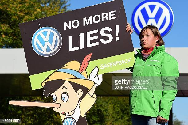An activist holds up a sign reading 'No more lies' during a protest of environmental watchdog Greenpeace in front of the headquarters of German car...