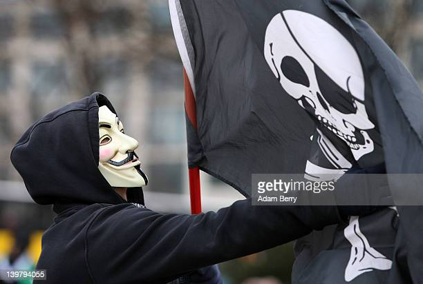 An activist in a Guy Fawkes mask adjusts a skull and crossbones flag during a demonstration against the AntiCounterfeiting Trade Agreement on...