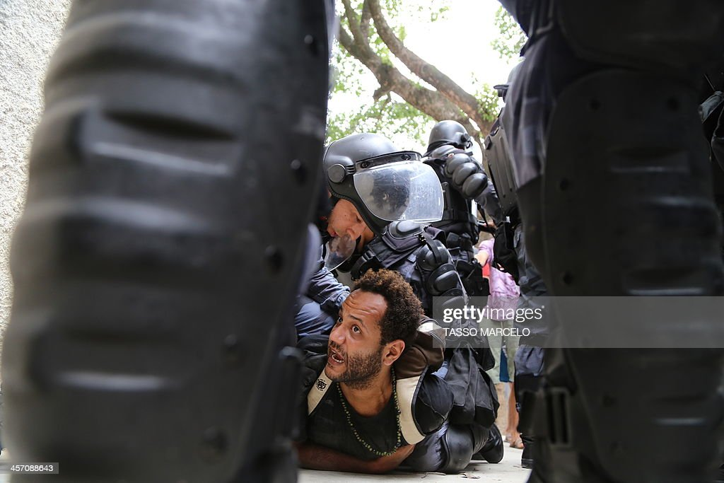 An activist is arrested by riot police during a demonstration near the Museu do Indio (Indian Museum) 'Aldea Maracana' (Maracana Village) in Rio de Janeiro, Brazil, on December 16, 2013. The demonstrators, among whom there were some 30 Amazonic natives, seized the museum protesting against its scheduled demolition to continue the works in the Mario Filho 'Maracana' stadium ahead of the FIFA WC Brazil 2014. AFP PHOTO/TASSO MARCELO