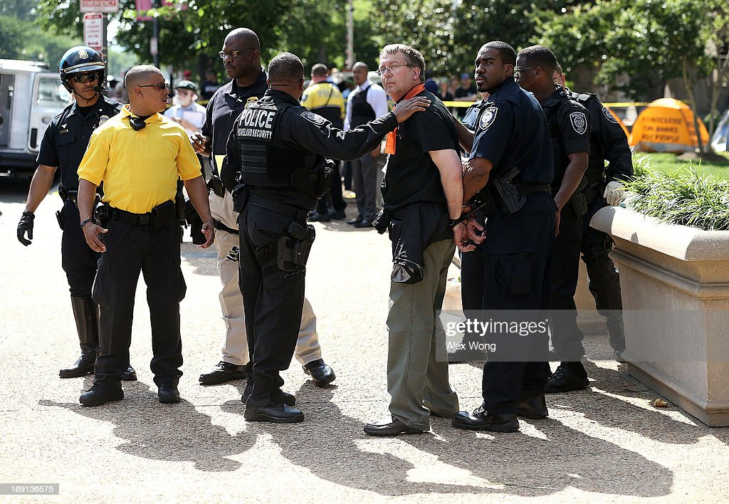 An activist is arrested by the police after he participated in civil disobedience during a protest outside the U.S. Justice Department May 20, 2013 in Washington, DC. Homeowners and activists from Home Defenders League and Occupy Homes joined the protest to demand that Attorney General Eric Holder 'hold Wall Street Banks that ravaged America's economy accountable.'