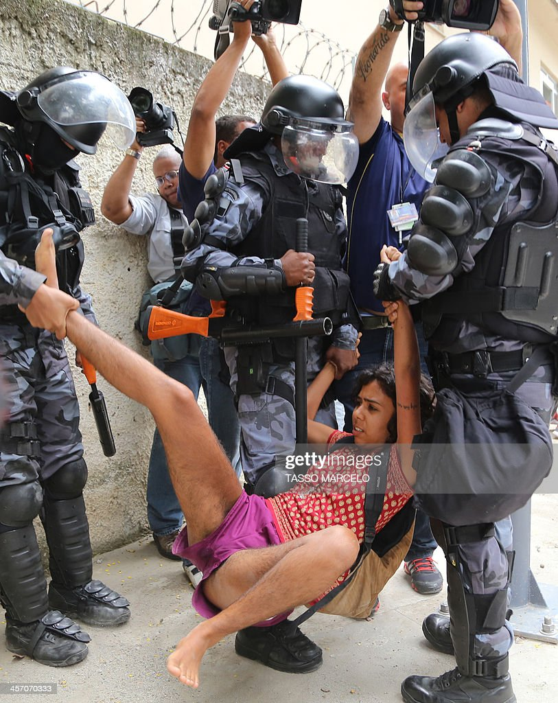 An activist is detained by riot police during a demonstration near the Museu do Indio (Indian Museum) 'Aldea Maracana (Maracana Village) in Rio de Janeiro, Brazil, on December 16, 2013. The demonstrators, among whom there were some 30 Amazonic natives, seized the museum protesting against its scheduled demolition as part of the works in the Mario Filho 'Maracana' stadium ahead of the FIFA WC Brazil 2014.