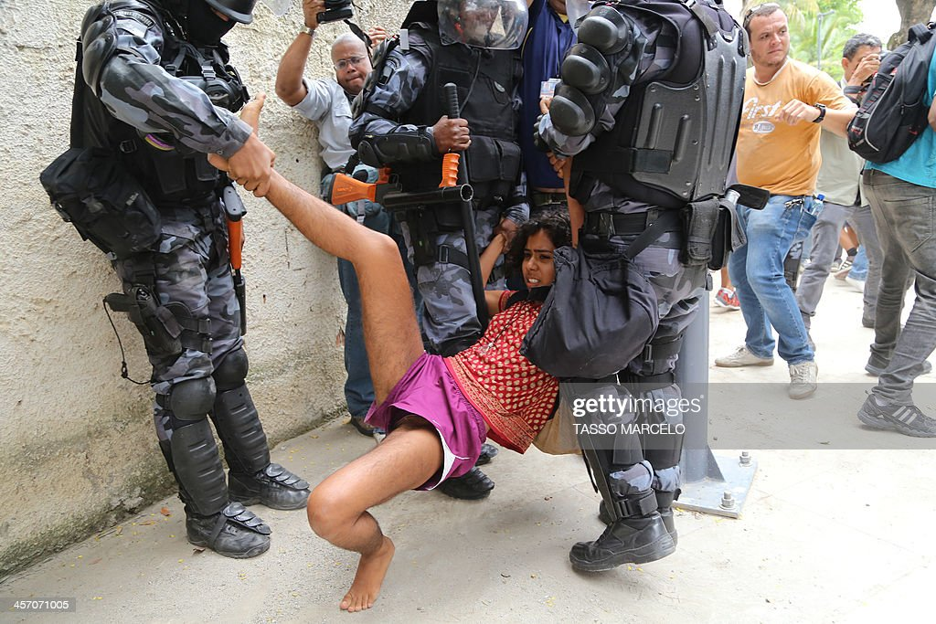 An activist is detained by riot police during a demonstration near the Museu do Indio (Indian Museum) 'Aldea Maracana' (Maracana Village) in Rio de Janeiro, Brazil, on December 16, 2013. The demonstrators, among whom there were some 30 Amazonic natives, seized the museum protesting against its scheduled demolition to continue the works in the Mario Filho 'Maracana' stadium ahead of the FIFA WC Brazil 2014.