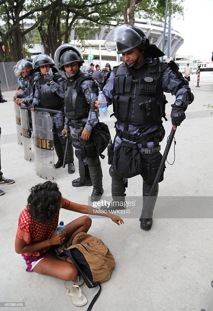 An activist is detained by riot police during a demonstration near the Museu do Indio (Indian Museum) 'Aldea Maracana' (Maracana Village) in Rio de Janeiro, Brazil, on December 16, 2013. The demonstrators, among whom there were some 30 Amazonic natives, seized the museum protesting against its scheduled demolition to continue the works in the Mario Filho 'Maracana' stadium ahead of the FIFA WC Brazil 2014. AFP PHOTO/TASSO MARCELO