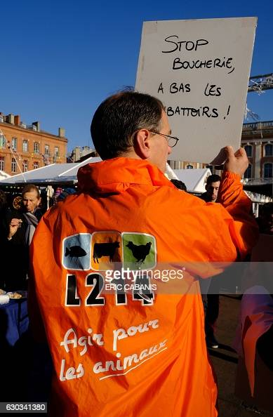 An activist of animal rights association L214 wearing a jacket reading 'Act for animals' and holding a sign reading 'Stop butchering stop to...