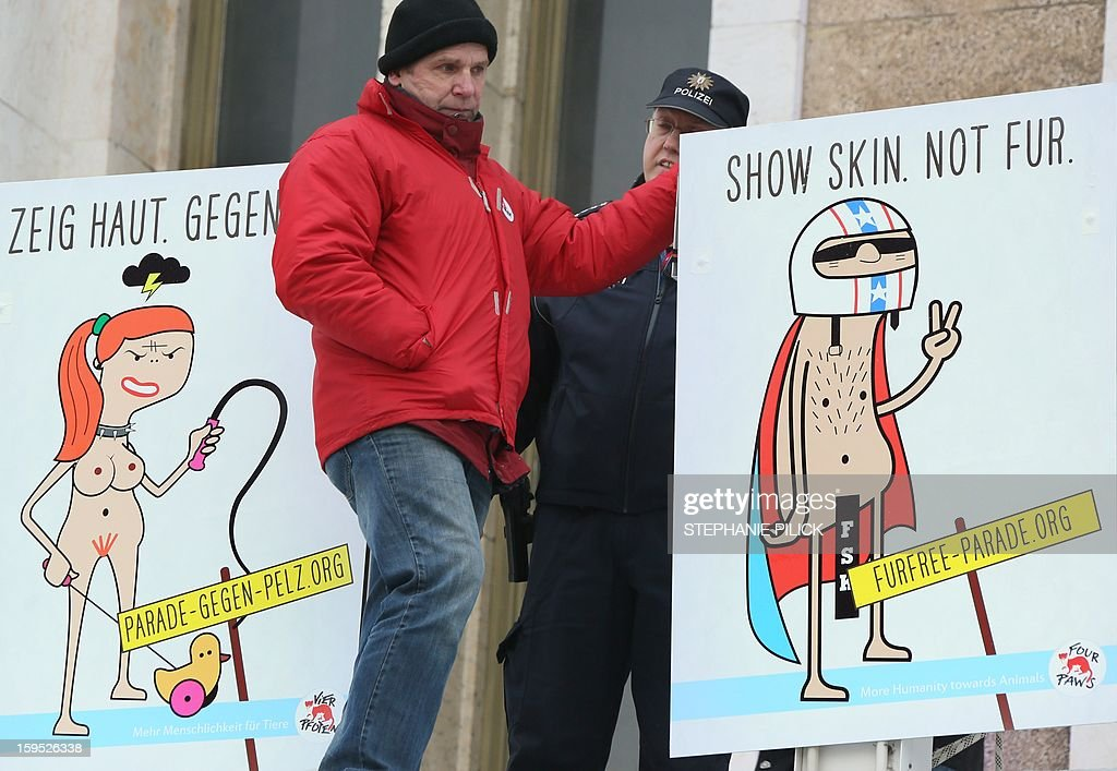 An activist of animal welfare organisation 'Four Paws' (Vier Pfoten) arranges placards reading 'Show skin. Not fur' next to a policeman at the former airport Tempelhof in Berlin, on January 13, 2013. The Fashion fair 'Bread and Butter' is located in the former airport and takes part from January 15 to 17, 2013. AFP PHOTO / STEPHANIE PILICK GERMANY OUT