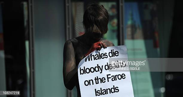 An activist of PETA with fake blood smeared on her holds a placard during protests against whaling at the Faroe Islands outside the Danish embassy on...