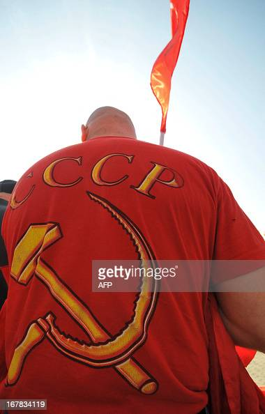 An activist of Russian Communist attends a traditional May Day Communist rally in the southern Russian city of Stavropol May 1 2013 The sign on the...