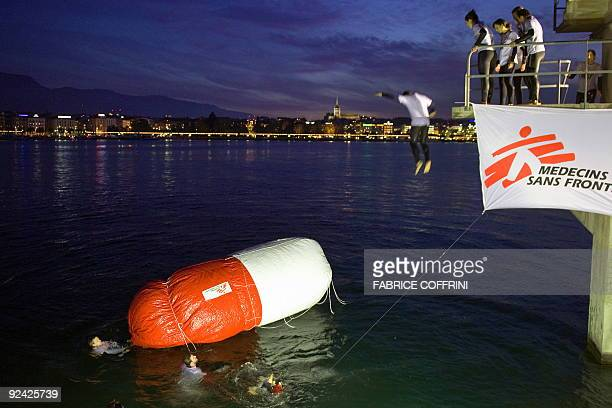 An activist of Swiss NGO 'Medecins Sans Frontiers' or 'MSF' jumps into Lake Geneva next to a giant inflated mock capsule during a demonstration on...