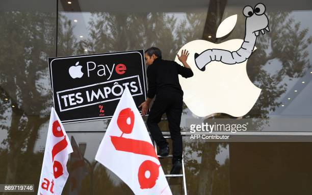 An activist of the Association for the Taxation of financial Transactions and Citizen's Action sticks a poster 'Apple pay your taxes' on the facade...