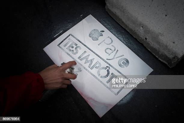 An activist of the 'Attac' sprays a slogan reading 'pay your taxes' on the sidewalk during a protest against tax evasion outside an Apple shop on the...