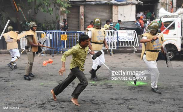 TOPSHOT An activist of the Bhartiya Janata Party runs past Indian police next to the state police headquarters in Kolkata on May 25 2017 The...