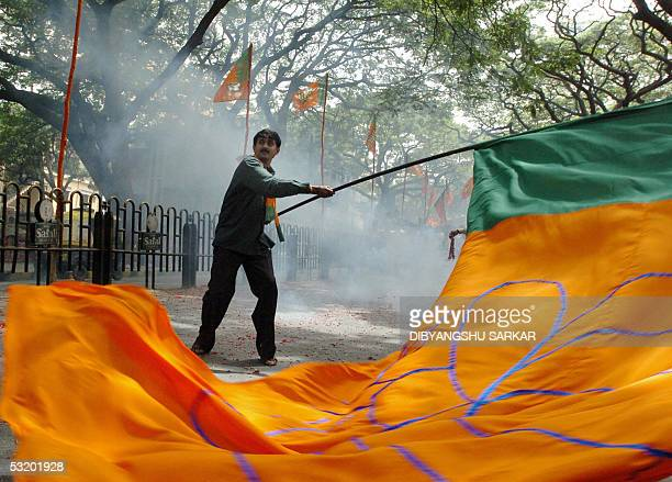 An activist of the Bhartiya Janta Party waves a party flag as he stands in the midst of smoke from firecrackers during a protest rally organised by...