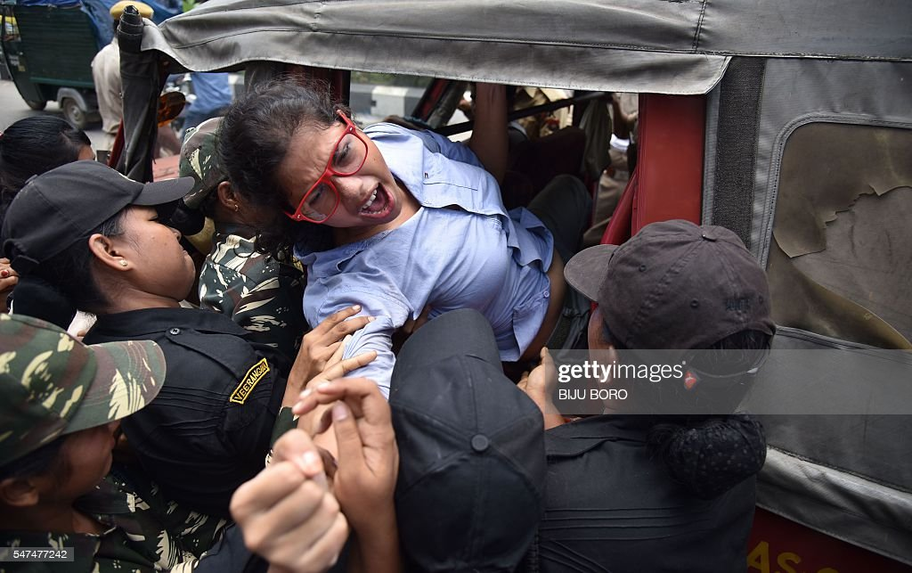 An activist of the Communist Party of India is forcefully carried away by police personnel during a protest against the Indian government decision to...