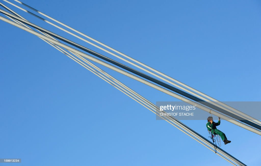 An activist of the environmental group 'Robin Wood' climbs on a roof pole of the Olympic hall in Munich, southern Germany to raise a banner that reads 'Siemens dams: expulsion, greed, enviromental destruction' as the German industrial giant Siemens holds its annual shareholder meeting on January 23, 2013. Robin Wood protests against the participation of Siemens at an embankment dam project in Brazil.