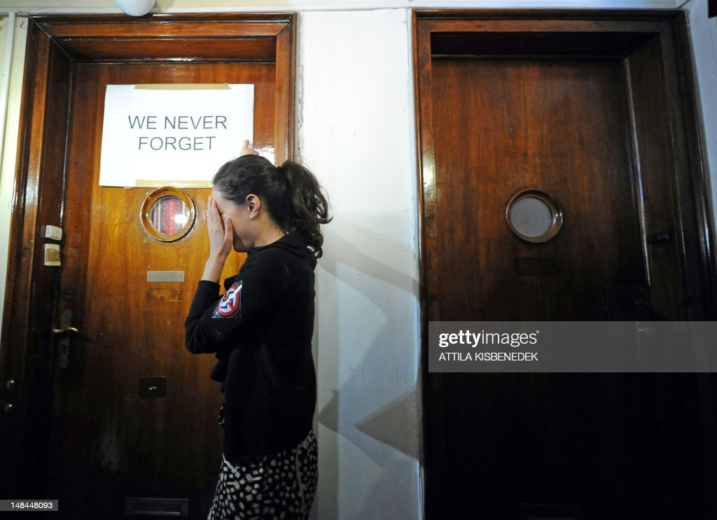 An activist of the European Union of Jewish Students organization wipes her face as she points to a banner with a protest slogan taped to the door of Csatary's hideaway building, only few kilometers from his home in Budapest on July 16, 2012 prior to their protest against Csatary called after a Hungarian prosecutor said that investigating an aged Nazi war criminal found alive and well in Budapest was problematic because the events took place so long ago and in a different country. A probe into Laszlo Csatary, 97, began in September after information was received from the Nazi-hunting Simon Wiesenthal Center, which ranks him number one on their wanted list, the public prosecutors' office said.