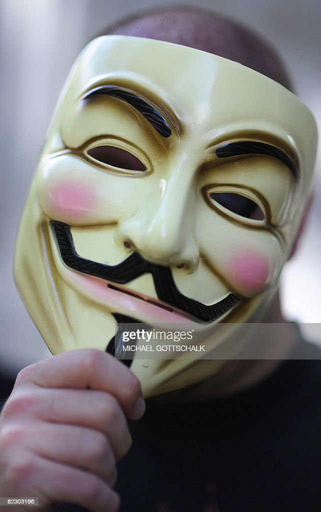 An activist of the organization 'Anonymous' holds a mask in front of his face on August 14, 2008 during a demonstration in Berlin. Members of 'Anonymous' aim to attract attention on dangerous totalitarian methods at the Church of Scientology. AFP PHOTO DDP/MICHAEL GOTTSCHALK GERMANY OUT
