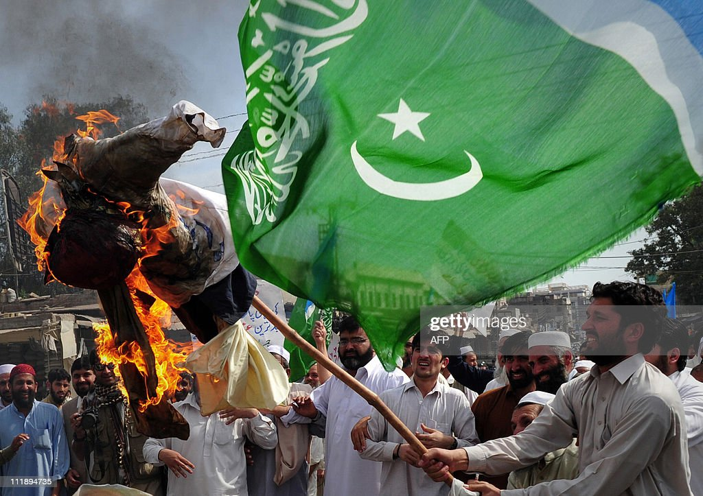 An activist of the Pakistani fundamentalist Islamic party JamaatiIslami holds a burning effigy of CIA contractor Raymond Davis during a protest in...
