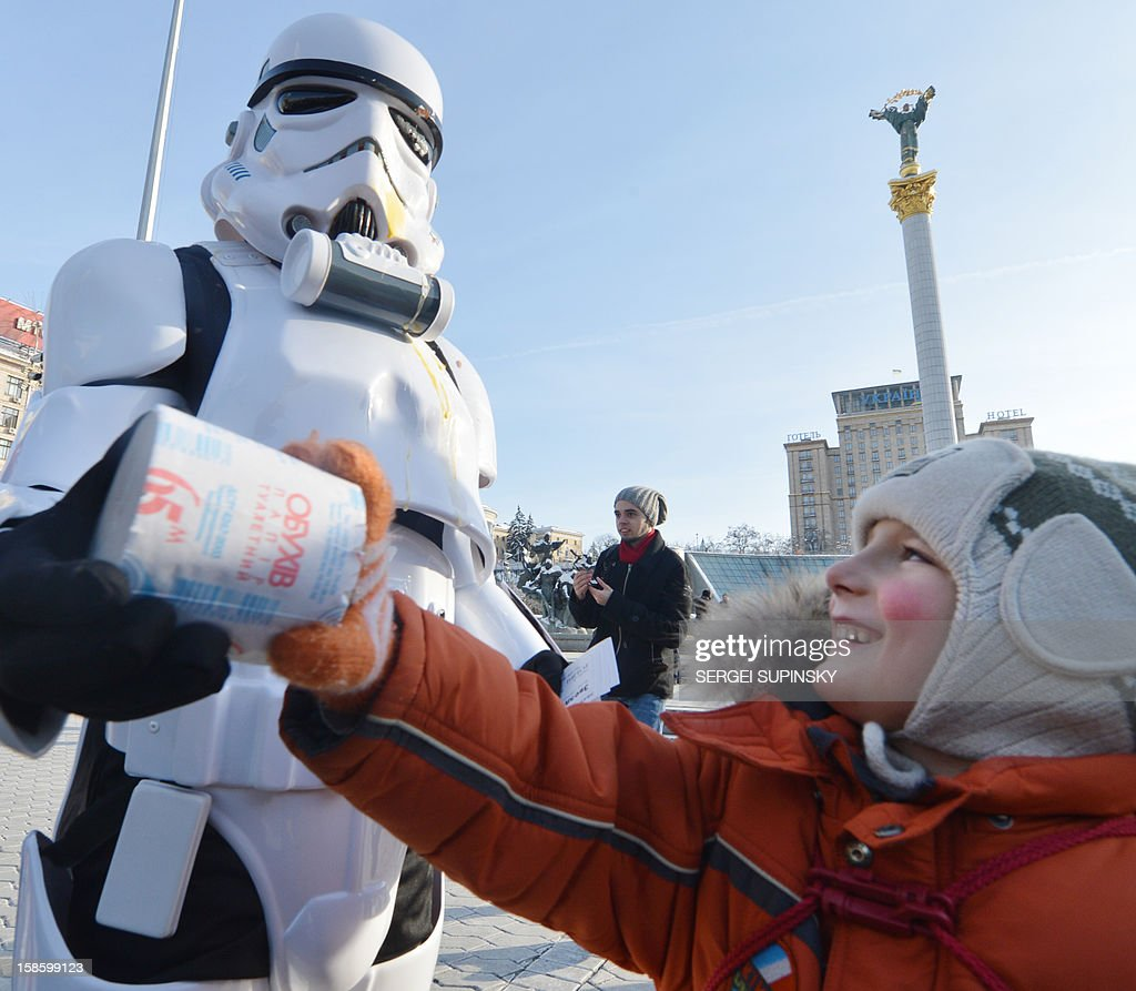 An activist of the Ukrainian Internet Party, wearing a stormtrooper outfit from the Star Wars saga, distributes toilet paper on December 20, 2012 on Independence Square in Kiev. The party activists, who traditionally wear Star Wars costumes during their actions, distributed canned foods, matches, condoms, toilet paper, soap, lightbulbs and 'tickets' for their spacecraft evacuation to passersby to supposedly save Ukrainians from the end of the world on December 21. The date marks the end of an era that lasted over 5,000 years, according to the Mayan 'Long Count' calendar. Some believe that the date, which coincides with the December solstice, marks the end of the world as foretold by Mayan hieroglyphs -- an idea ridiculed by scholars.