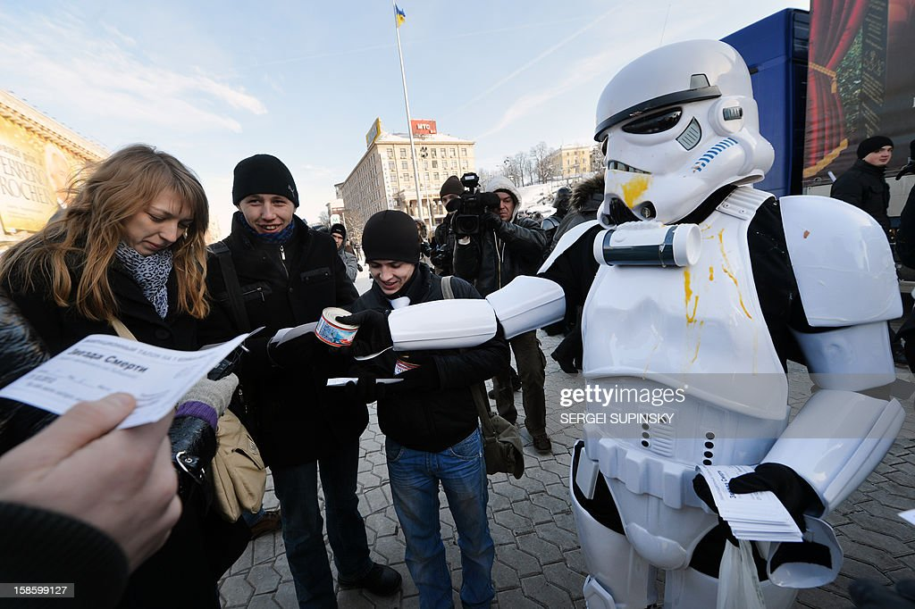 An activist of the Ukrainian Internet Party, wearing a stormtrooper outfit from the Star Wars saga, distributes leaflets on December 20, 2012 on Independence Square in Kiev. The party activists, who traditionally wear Star Wars costumes during their actions, distributed canned foods, matches, condoms, toilet paper, soap, lightbulbs and 'tickets' for their spacecraft evacuation to passersby to supposedly save Ukrainians from the end of the world on December 21. The date marks the end of an era that lasted over 5,000 years, according to the Mayan 'Long Count' calendar. Some believe that the date, which coincides with the December solstice, marks the end of the world as foretold by Mayan hieroglyphs -- an idea ridiculed by scholars.