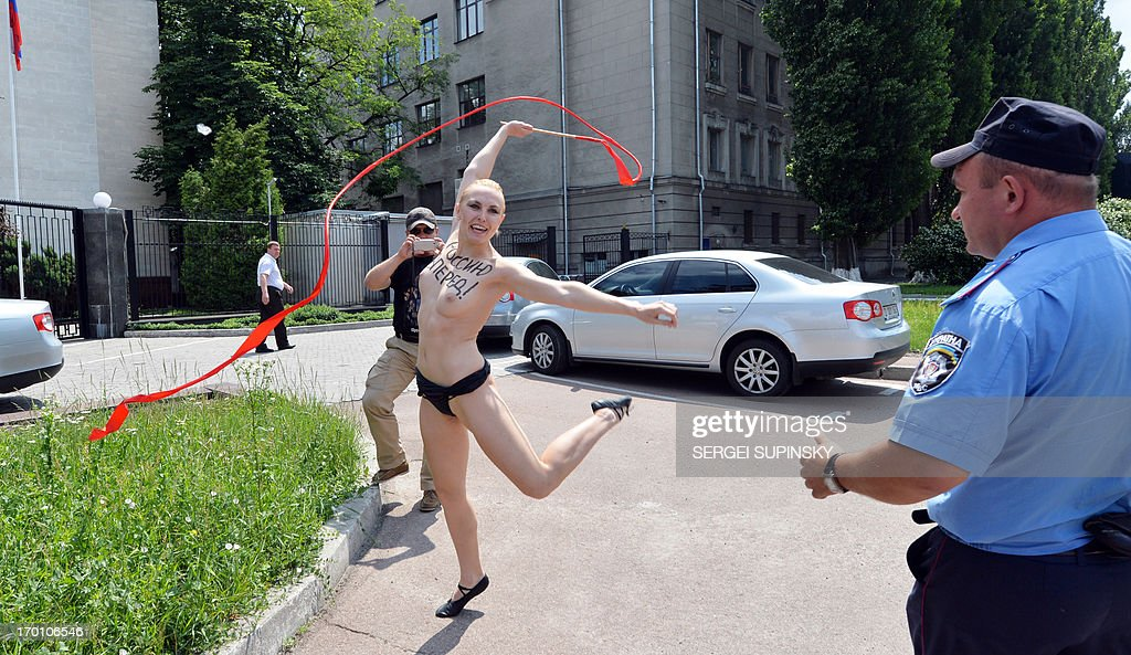 An activist of the women's feminist organization Femen, with the word 'Forward Russia !' written on her torso, shouts 'Vladimir I love you!' performs with a ribbon an impersonation of Russian gymnast Alina Kabayeva, as a policeman runs to arrest her during an action held outside the Russian embassy in Kiev on June 7, 2013. Russian President Vladimir Putin and his wife Lyudmila on June 7 announced their divorce after three decades of marriage, in a stunning revelation that ended years of speculation about their union. The Moskovsky Korrespondent newspaper, owned by tycoon Alexander Lebedev, reported in 2008 that Vladimir Putin was about to marry Olympic gymnast turned legislator Alina Kabayeva, 31 years his junior. AFP PHOTO/ SERGEI SUPINSKY
