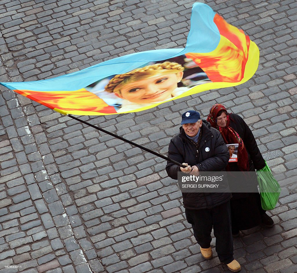 An activist of Ukrainian opposition waves a flag witha portrait of jailed former prime-minister Yulia Tymoshenko march during mass march and rally called 'Kievites against political repression!' in Kiev on February 25, 2012. Ukraine President Viktor Yanukovych flies to Brussels for a summit Monday seen as 'a defining moment' in a long-delayed bid to seal a political and trade pact with the EU anchoring the ex-Soviet state closer to the West.