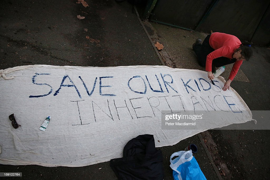 An activist paints a banner at Battersea Park adventure playground on January 8, 2013 in London, England. Activists and local residents oppose local authority plans to demolish the adventure playground, which has been mostly used by teenagers, and replace it with facilities for younger children who will need less supervision.