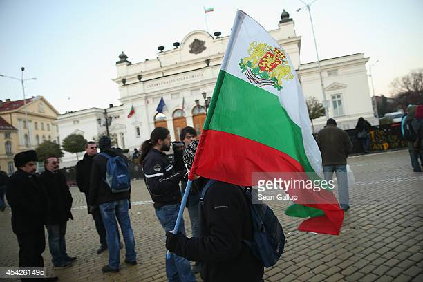 An activist protesting against government and police corruption carries a Bulgarian flag as he walks past the Bulgarian Parliament Building on...