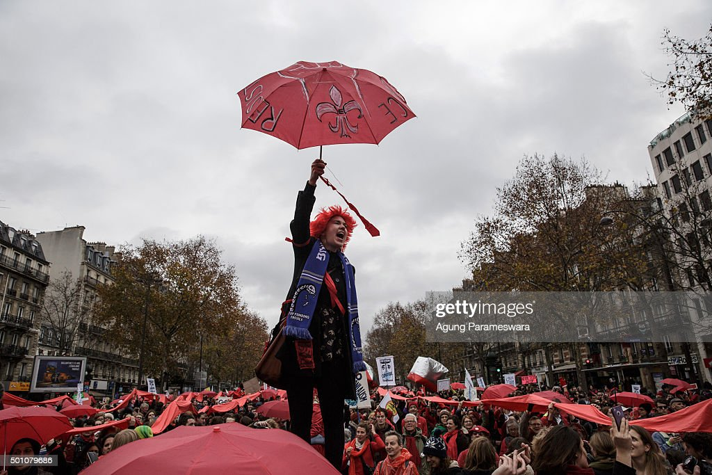 An activist shouts as she hold up an umbrella during a demonstration near the Arc de Triomphe at the Avenue de la Grande Armee boulevard on December 12, 2015 in Paris, France. The final draft of a 195-nation landmark agreement on climate has been submitted at the United Nations conference on climate change COP21, aimed at limiting greenhouse gas emissions and keeping planetary warming below 2.0 degrees Celsius.