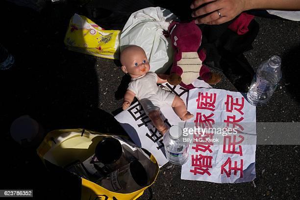 An activist shows a baby doll during the march to protest against proposal to legalize samesex marriage outside The Legislative Yuan of Republic of...