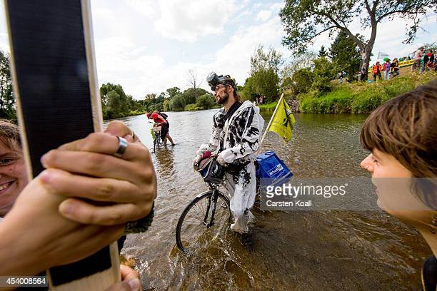 An activist sits on his bicycle as other activists protest in a line in the borderriver Neisse against the expansion of nearby openpit coal mines...