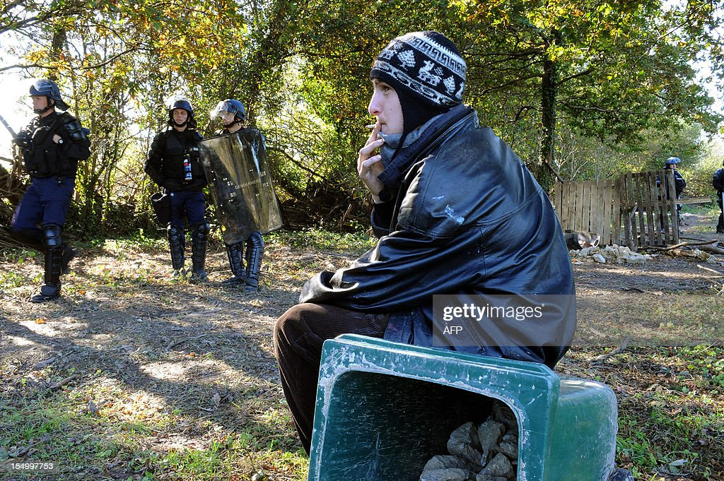 An activist smokes a cigarette in front of French gendarmes during an important evacuation operation of houses squatted by opponents against a project to build an international airport, on October 30, 2012 in Notre-Dame-des-Landes, western France. The project was signed in 2010 and the international airport is supposed to open in 2017 near the city of Nantes.
