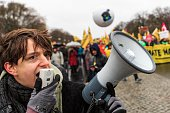 An activist speaks into a megaphone during the Global Climate March on November 29 2015 in Berlin Germany The COP21 2015 Paris Climate Conference...