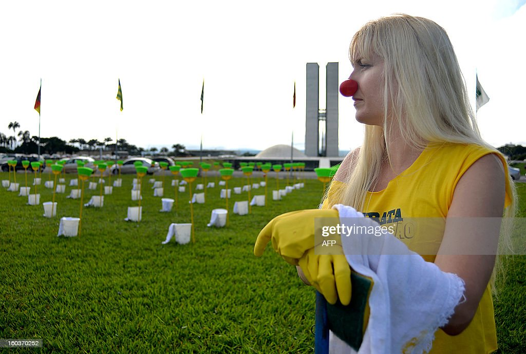 An activist stands by 81 cleaning kits consisting each in a broom, a bucket and a duster placed in front of the Brazilian National Congress, in Brasilia, on January 30, 2013. The demonstration is organized by Rio de Janeiro's 'River of Peace' movement and the 81 cleaning kits --the number of senators of in the national congress-- symbolizes the need for 'cleaning' the senate of corruption. This week the presidential election will be held in the federal senate and the favorite candidate, senator Renan Calheiros, has been the target of many accusations of corruption.