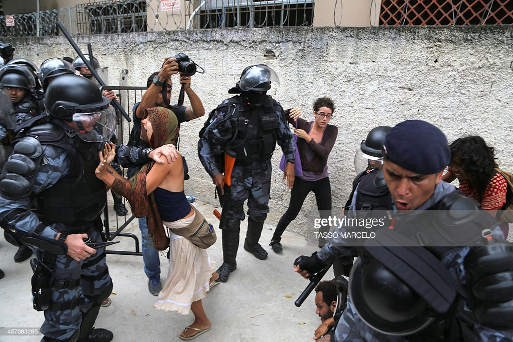 An activist struggles with riot police during a demonstration near the Museu do Indio (Indian Museum) 'Aldea Maracana' (Maracana Village) in Rio de Janeiro, Brazil, on December 16, 2013. The demonstrators, among whom there were some 30 Amazonic natives, seized the museum protesting against its scheduled demolition to continue the works in the Mario Filho 'Maracana' stadium ahead of the FIFA WC Brazil 2014. AFP PHOTO/TASSO MARCELO