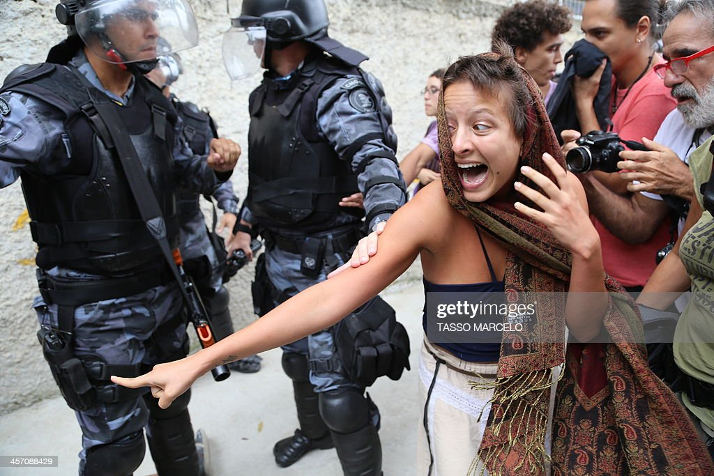 An activist struggles with riot police during a demonstration near the Museu do Indio (Indian Museum) 'Aldea Maracana' (Maracana Village) in Rio de Janeiro, Brazil, on December 16, 2013. The demonstrators, among whom there were some 30 Amazonic natives, seized the museum protesting against its scheduled demolition to continue the works in the Mario Filho 'Maracana' stadium ahead of the FIFA WC Brazil 2014.