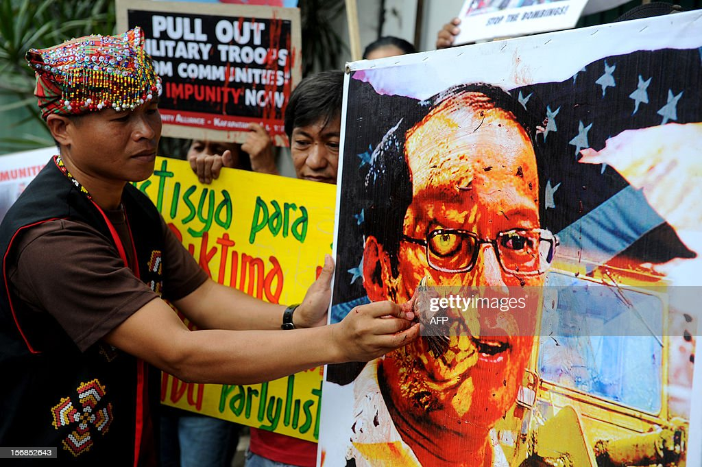 An activist uses a severed chicken head to paint with blood the picture of Philippine President Benigno Aquino during a protest against impunity in front of the house of the president in Manila on November 23, 2012, during the third anniversary of the infamous November 23 massacre in Maguindanao province. Human Rights Watch on November 22 urged Aquino to do more to break up private armed groups, three years after 58 people were killed in the country's worst political massacre.