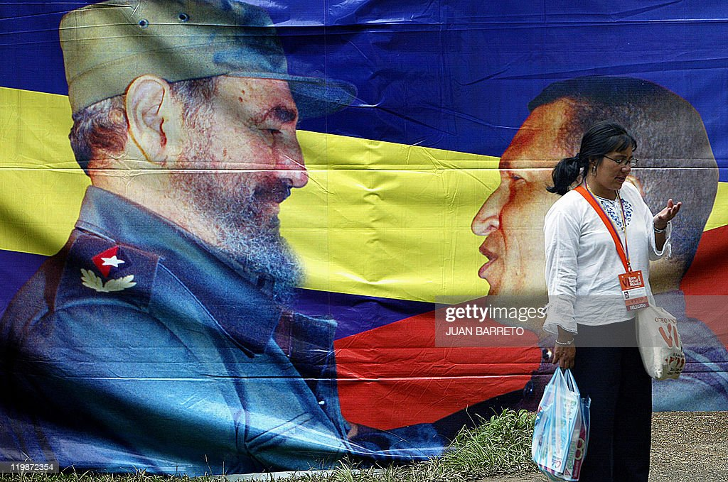 An activist walks by a banner with an image of Cuban President Fidel Castro and his Venezuelan counterpart Hugo Chavez 28 January 2006 in Caracas...